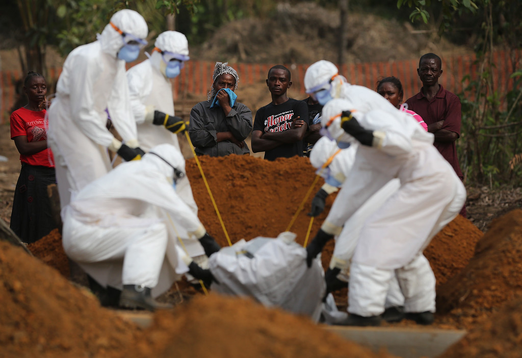 ". A family watches as a burial team lowers their loved one into a grave at the U.S.-built cemetery for ""safe burials\"" on January 27, 2015 in Disco Hill, Liberia. The cemetery, operated by USAID-funded Global Communities, has buried almost 300 people in its first month of operation, with increasingly fewer of the bodies coming from Ebola Treatment Units (ETUs), as infection rates decline. The cemetery, where burial team members wear protective clothing (PPE), has been seen in Monrovia as a major achievement, as families of deceased loved ones are permitted to view the burials, important in Liberian culture. In an effort to control the Ebola epidemic in 2014, the Liberian government had ordered the cremation of all deceased in the capital, often further traumatizing surviving family members and unintentionally encouraging many families to hide their dead for secret burials.  (Photo by John Moore/Getty Images)"