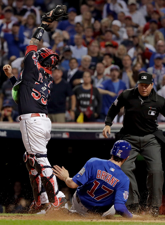. Chicago Cubs\' Kris Bryant, right, scores past Cleveland Indians catcher Roberto Perez on a hit by Anthony Rizzo during the fifth inning of Game 7 of the Major League Baseball World Series Wednesday, Nov. 2, 2016, in Cleveland. (AP Photo/Matt Slocum)