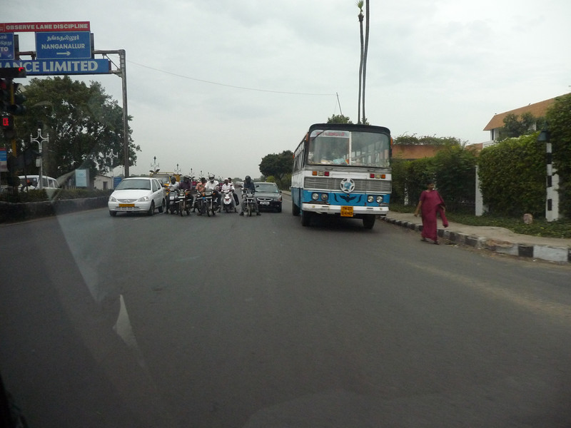 a few vechicles actually stop for a traffic light.  The bus is typical of Chenai's mass transit fleet.