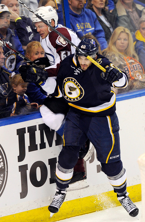 . St. Louis Blues\' Maxime Lapierre (40) checks Colorado Avalanche\'s Andre Benoit during the third period of an NHL hockey game, Saturday, April 5, 2014, in St. Louis. (AP Photo/Bill Boyce)