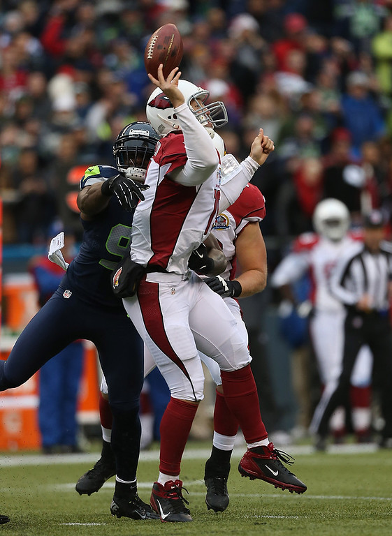 . Quarterback John Skelton #19 of the Arizona Cardinals is hit as he throws by defensive end Chris Clemons #91 of the Seattle Seahawks at CenturyLink Field on December 9, 2012 in Seattle, Washington.  (Photo by Otto Greule Jr/Getty Images)
