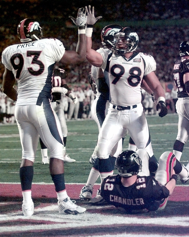 . Denver Broncos defensive end Trevor Pryce (93)  gives defensive tackle Maa Tanuvasa a high five during Super Bowl XXXIII action against the Atlanta Falcons in Miami, Sunday, Jan. 31, 1999. Falcons quarterback Chris Chandler is at bottom right.  (AP Photo/Dave Martin)