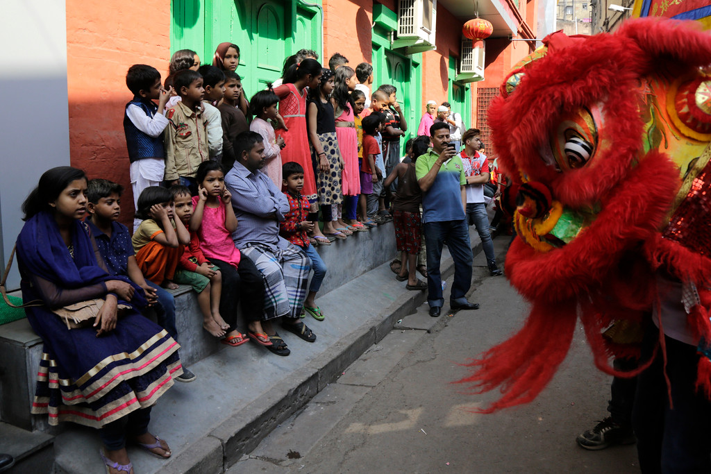 . Resident Indians watch as ethnic Chinese people perform lion dance on the first day of Lunar New Year in Kolkata, India, Friday, Feb. 16, 2018. People in Asia and around the world are celebrating the Lunar New Year on Friday with festivals, parades and temple visits to ask for blessings. This year marks the year of the dog, one of the 12 animals in the Chinese astrological chart. (AP Photo/Bikas Das)
