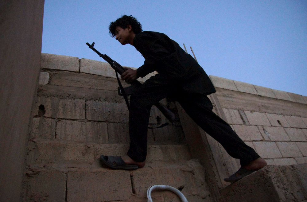 . An armed Free Syrian Army fighter takes his position on top of a building in Deir al-Zor April 16, 2013.  REUTERS/ Khalil Ashawi
