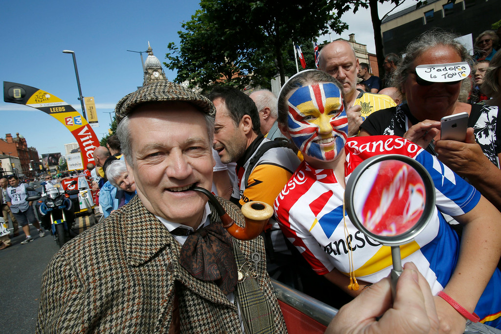 . A man dressed as Sherlock Holmes, the fictional detective created by Scottish author and physician Sir Arthur Conan Doyle, left, poses with cycling fans prior to the start of the first stage of the Tour de France cycling race over 190.5 kilometers (118.4 miles) with start in Leeds and finish in Harrogate, Britain, Saturday, July 5, 2014. (AP Photo/Christophe Ena)