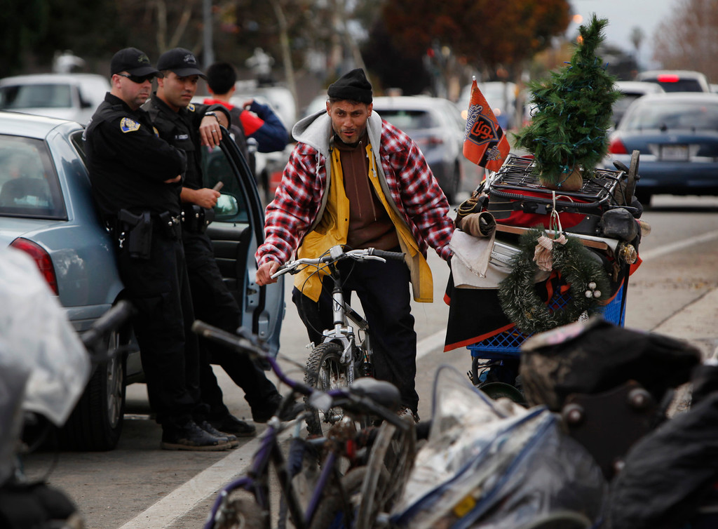 . Two police officers watch Ricardo Lopez tow his shopping cart filled with his belongings and a Christmas tree as he leaves The Jungle homeless camp in San Jose, Calif., looking for a place to stay Thursday afternoon, Dec. 4, 2014. Lopez has lived in the notorious homeless camp for two and a half years and was evicted with others when the city closed the camp. (Karl Mondon/Bay Area News Group)