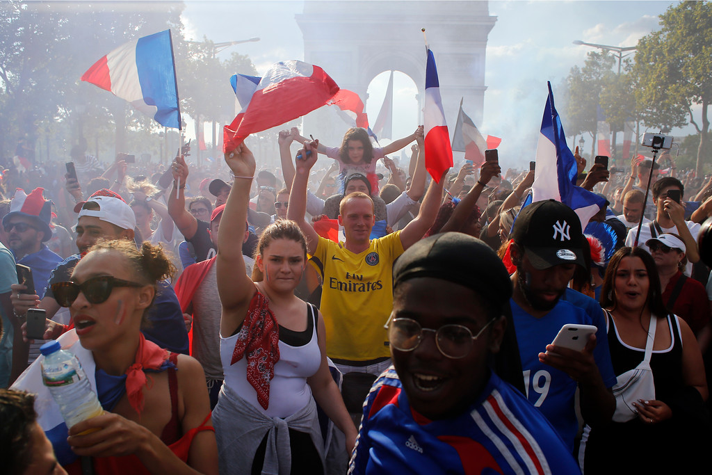 . People react on the Champs Elysees avenue with the Arc de Triomphe on background, after France defeated Croatia in the final match at the 2018 soccer World Cup, in Paris, France, Sunday, July 15, 2018. France won the final 4-2. (AP Photo/Thibault Camus)