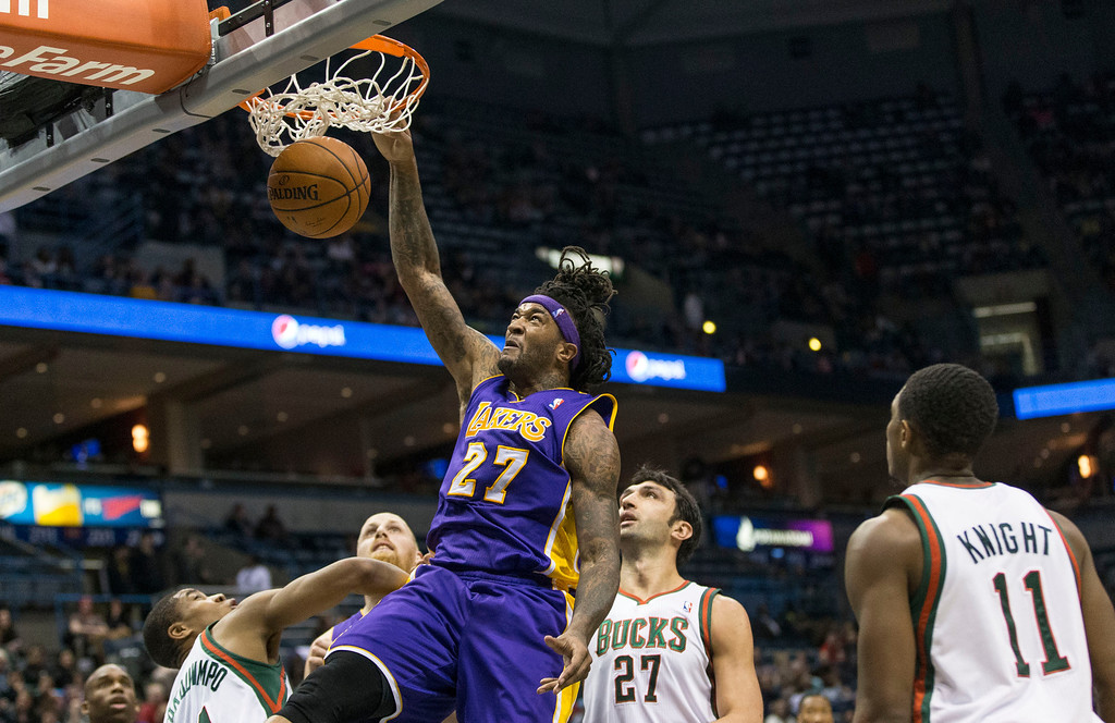 . Los Angeles Lakers\' Jordan Hill dunks as the Milwaukee Bucks defenders look on during the first half of an NBA basketball game Thursday, March 27, 2014, in Milwaukee. (AP Photo/Tom Lynn)