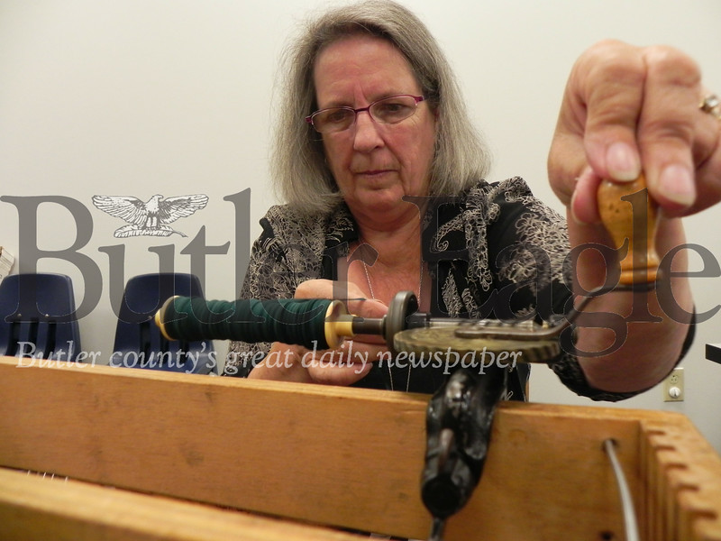 Susan Lightner, of Marion Township and Butler Spinners and Weavers Guild member, weaves a handbag on her table top loom. Photo by Gabriella Canales.