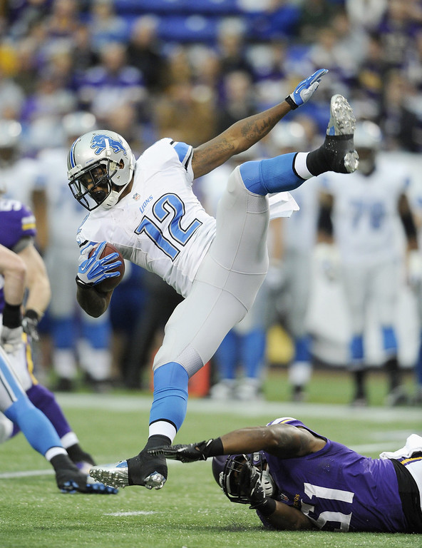 . Larry Dean #51 of the Minnesota Vikings tackles Jeremy Ross #12 of the Detroit Lions during the first quarter of the game on December 29, 2013 at Mall of America Field at the Hubert H. Humphrey Metrodome in Minneapolis, Minnesota. (Photo by Hannah Foslien/Getty Images)