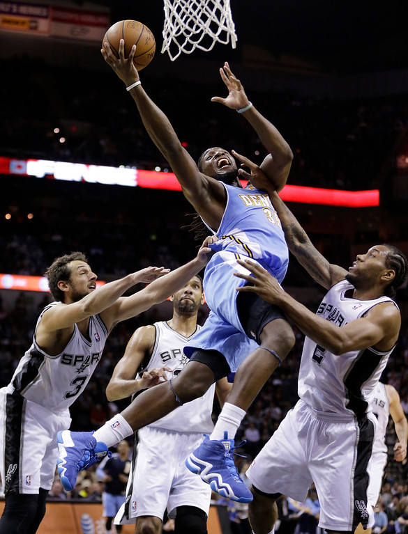 . Denver Nuggets\' Kenneth Faried (35) drives to the basket between San Antonio Spurs\'  Marco Belinelli (3), of Italy, Tim Duncan, center, and Kawhi Leonard, right, during the second half of an NBA basketball game, Wednesday, March 26, 2014, in San Antonio. San Antonio won 108-103. (AP Photo/Eric Gay)