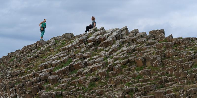Tourists on basalt rocks, Giants Causeway, County Antrim, Northern Ireland, United Kingdom