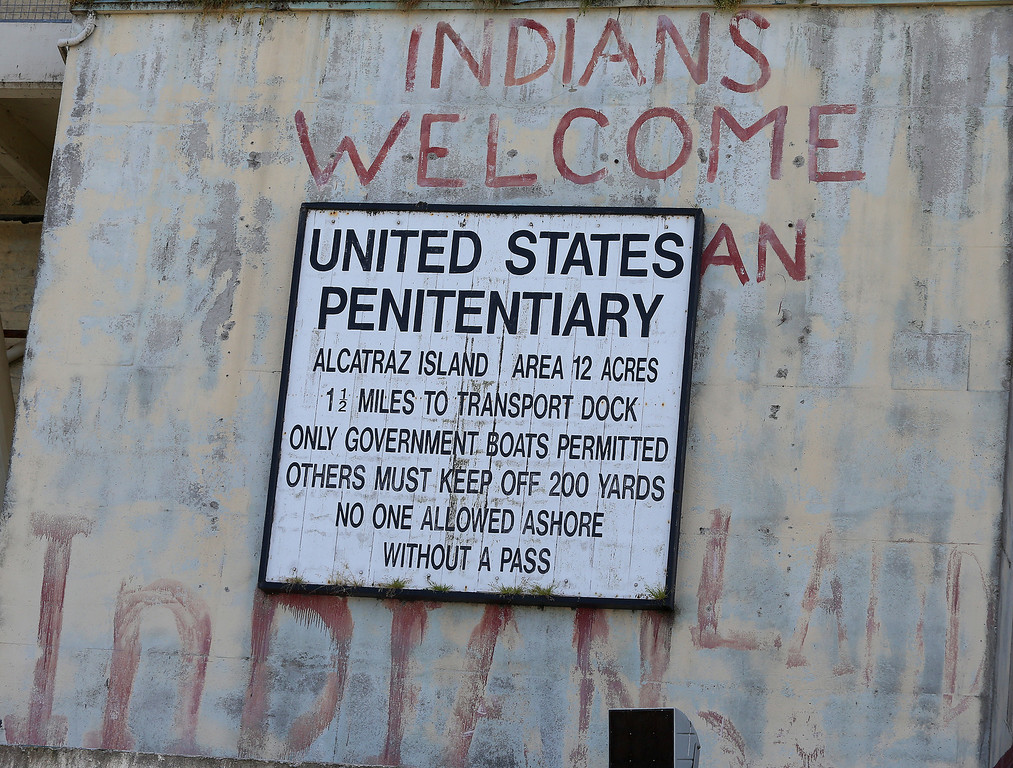 . A prison sign is photographed along with a hand painted sign refering to one of three Native American occupations of Alcatraz Island on Monday, March 18, 2013 in San Francisco, Calif.     The federal prison on the island closed 50 years ago and is now a tourist destination.  (Aric Crabb/Staff)