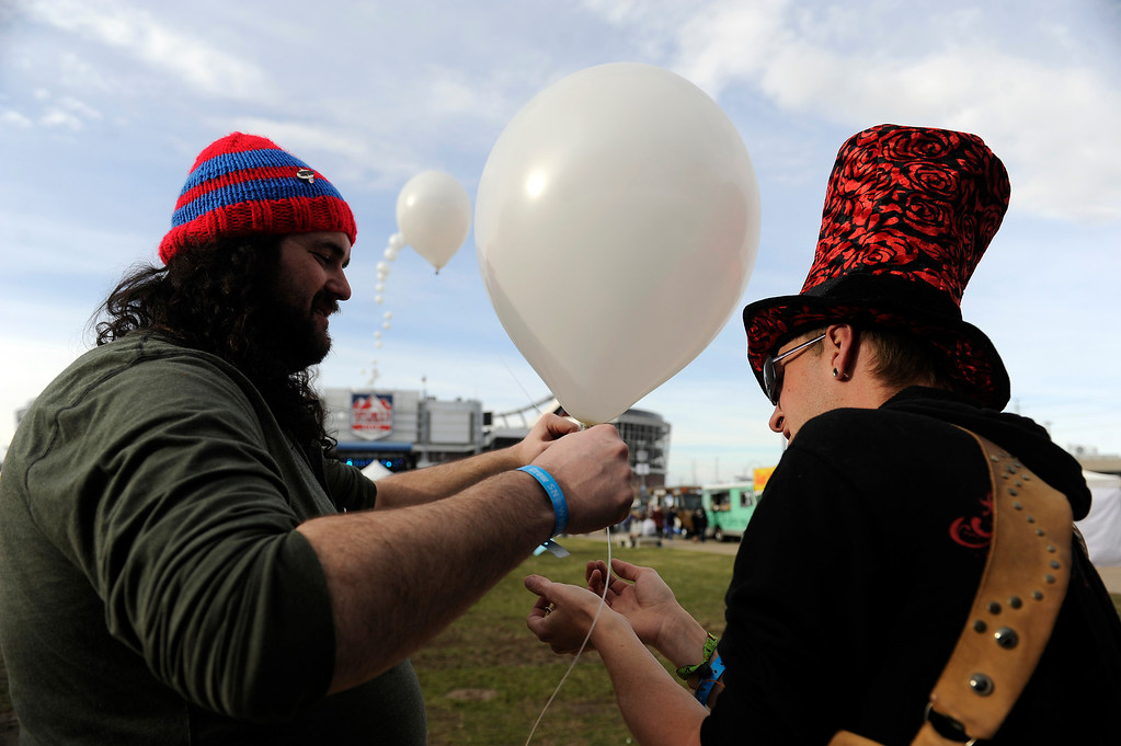 . DENVER, CO - APRIL 4: Moonshine Shorey, left, Sir Pluto of Balloon Chain make a led balloon chain during the Snowball Music Festival at Sports Authority Field at Mile High Stadium on April 4, 2014 in Denver, Colorado. The Snowball Music Festival is celebrating its first year in Denver after spending the previous three years as a mountain based festival. (Photo by Seth McConnell/The Denver Post)