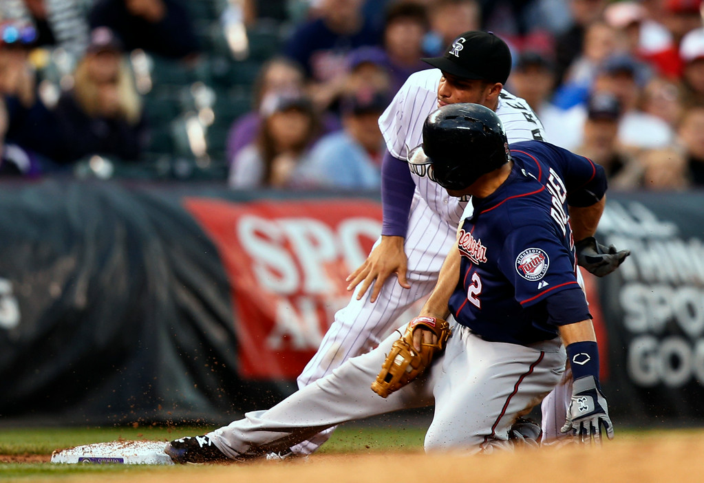 . Colorado Rockies third baseman Nolan Arenado (28) applies the tag to Minnesota Twins\' Brian Dozier (2) during the third inning of a baseball game on Friday, July 11, 2014, in Denver. (AP Photo/Jack Dempsey)