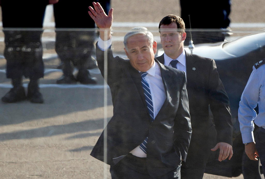 . Israel\'s Prime Minister Benjamin Netanyahu waves from behind protective glass as he arrives at a graduation ceremony for new pilots in the Hatzerim air force base near the city of Beersheba, southern Israel, Thursday, Dec. 26, 2013. (AP Photo/Ariel Schalit)