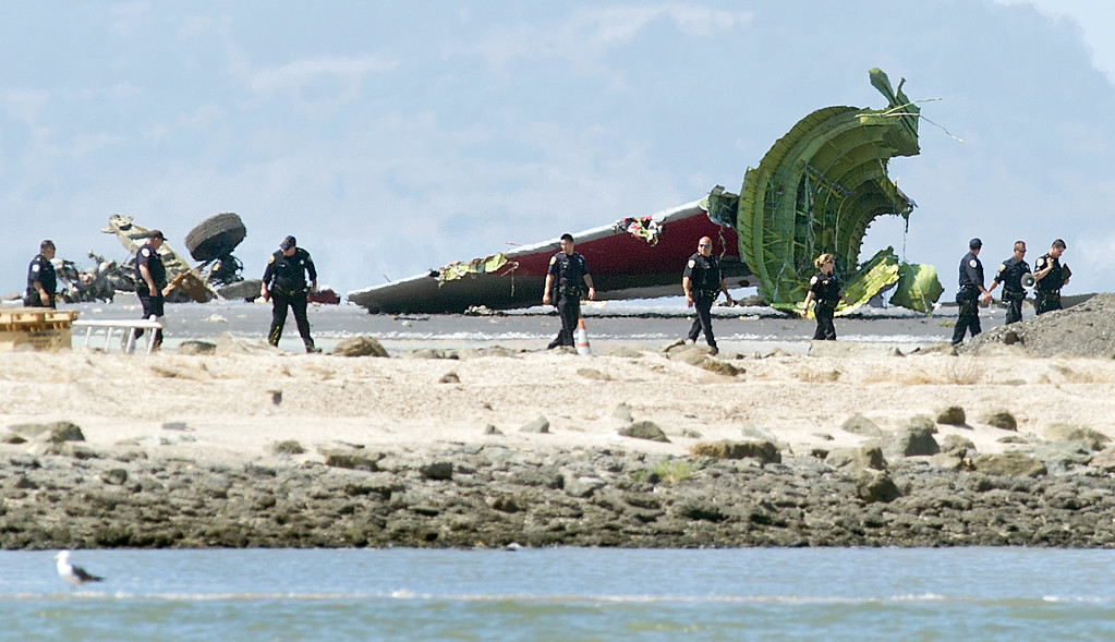 . Investigators pass the detached tail and landing gear of Asiana Flight 214 after it crashed at San Francisco International Airport on Saturday, July 6, 2013, in San Francisco. (AP Photo/Noah Berger)