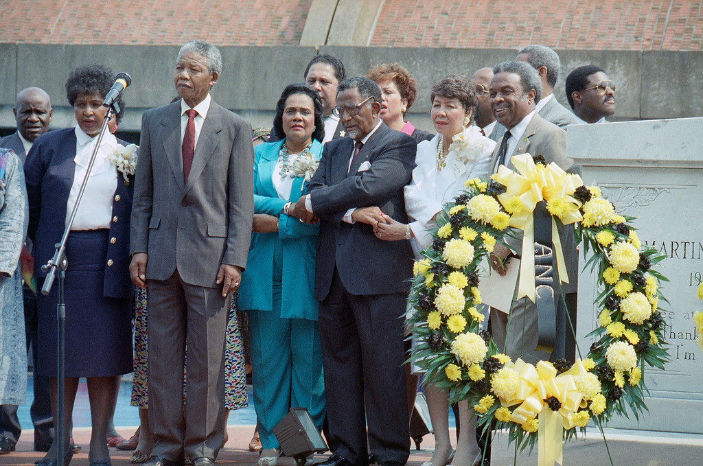 . Nelson Mandela pauses after laying a wreath at the tomb of the Rev. Martin Luther King Jr. in Atlanta Wednesday, June 28, 1990.    From left are: Winnie Mandela, Nelson Mandela, King\'s widow Coretta Scott King, the Rev. Joseph Lowery, President of the Southern Christian Leadership Conference, and Evelyn Lowery.  Man to right of Mrs. Lowery is unidentified. (AP Photo/Charles Kelly)