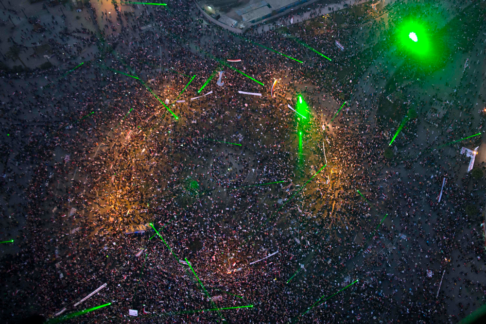 . This aerial image made from an Egyptian army helicopter shows a general view of green lasers lighting up a pro-military rally marking the third anniversary of the uprising that toppled autocrat Hosni Mubarak in Tahrir Square in Cairo, Egypt, Saturday, Jan. 25, 2014. Egyptian riot police have fired tear gas to disperse hundreds of supporters of ousted Islamist President Mohammed Morsi protesting as the country marks the third anniversary of the 2011 uprising, as supporters of the military gathered in rival rallies in other parts of the capital, many of them urging military chief Gen. Abdel-Fattah el-Sissi, the man who removed Morsi, to run for president.(AP Photo/Hassan Ammar)
