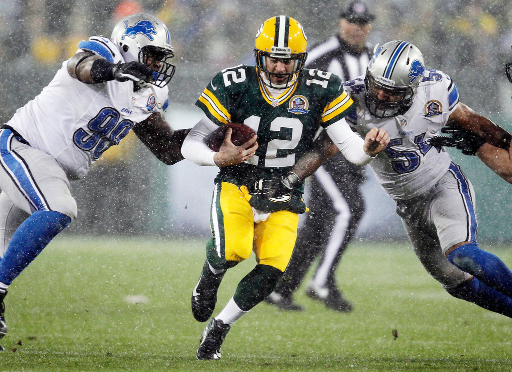 . Green Bay Packers quarterback Aaron Rodgers (12) tries to run between Detroit Lions\' Nick Fairley (98) and DeAndre Levy (54) during the first half of an NFL football game Sunday, Dec. 9, 2012, in Green Bay, Wis. (AP Photo/Mike Roemer)