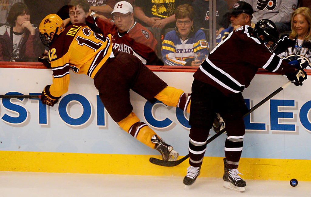 . Minnesota senior defenseman Justin Holl, left, goes flying after coming in contact with Union College senior forward Daniel Carr in the first period of the NCAA Frozen Four Championship Game at the Wells Fargo Center in Philadelphia, Saturday, April 12, 2014.  (Pioneer Press: John Autey)