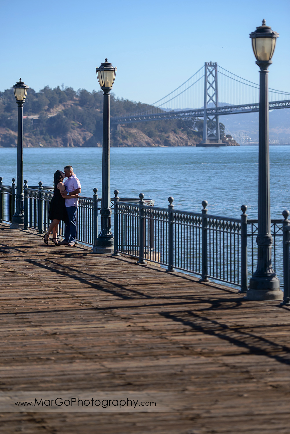 engagement session at Pier 7 in San Francisco - couple kissing with Bay Bridge in the background