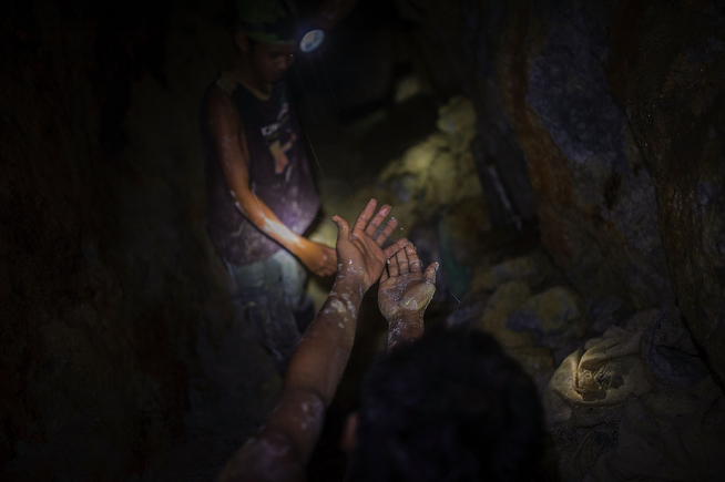 . Gold miners wash their muddy hands in the drip-water falling from the ceiling of an active tunnel. Water continuously leaks through the cracked stone walls of the tunnels and the miners are soaked all day, on April 22, 2014 in Pinut-An, Philippines. (Photo by Luc Forsyth/Getty Images)