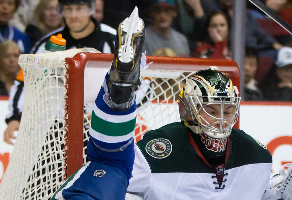 . Minnesota Wild goalie Darcy Kuemper, right, reacts as Vancouver Canucks\' Brad Richardson goes flying after being tripped up in front of the net during the first period of an NHL hockey game Friday, Feb. 28, 2014, in Vancouver, British Columbia. (AP Photo/The Canadian Press, Darryl Dyck)