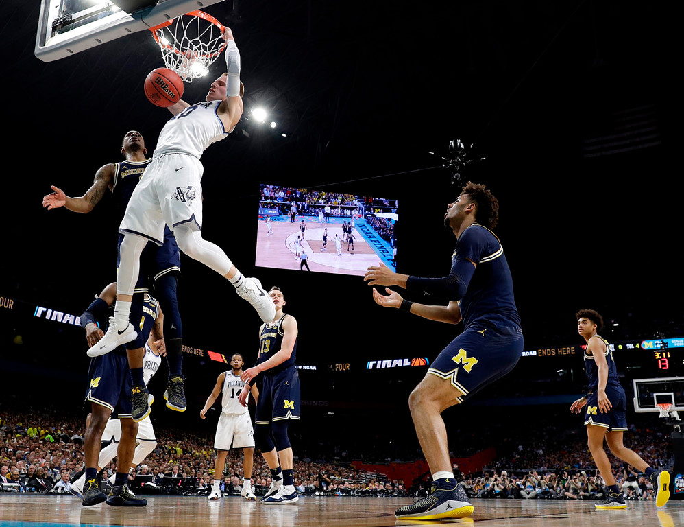 . Villanova guard Donte DiVincenzo dunks the ball over Michigan guard Charles Matthews during the first half in the championship game of the Final Four NCAA college basketball tournament, Monday, April 2, 2018, in San Antonio. (AP Photo/Eric Gay)