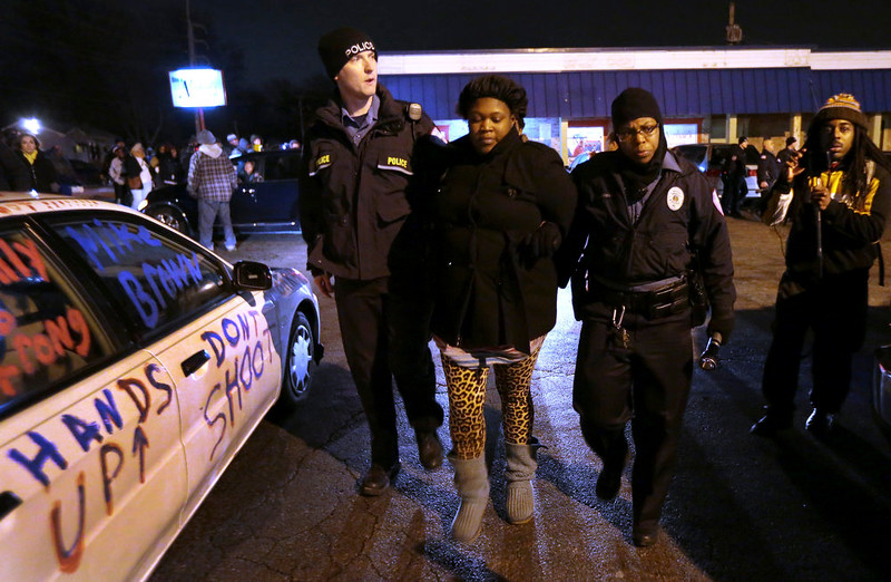 . A woman walks with police near a gas station in Berkeley, Mo., on Wednesday, Dec. 24, 2014. The mayor of the St. Louis suburb of Berkeley urged calm Wednesday after a white police officer killed black 18-year-old Antonio Martin who police said pointed a gun at him, reigniting tensions that have lingered since the death of Michael Brown in neighboring Ferguson. (AP Photo/St. Louis Post-Dispatch, Robert Cohen)