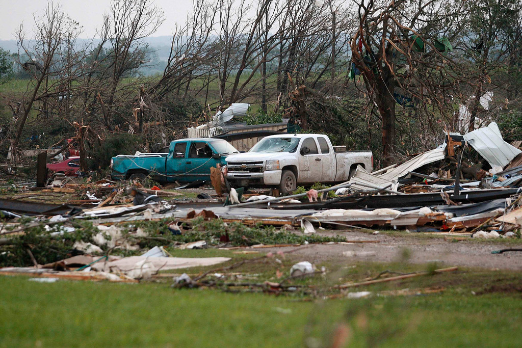 . Vehicles are seen amongst storm debris, which is what is left of a mobile home park destroyed by a tornado, west of Shawnee, Oklahoma May 19, 2013. A tornado half a mile wide struck near Oklahoma City on Sunday, part of a massive storm front that hammered the central United States. News reports said at least one person had died. REUTERS/Bill Waugh