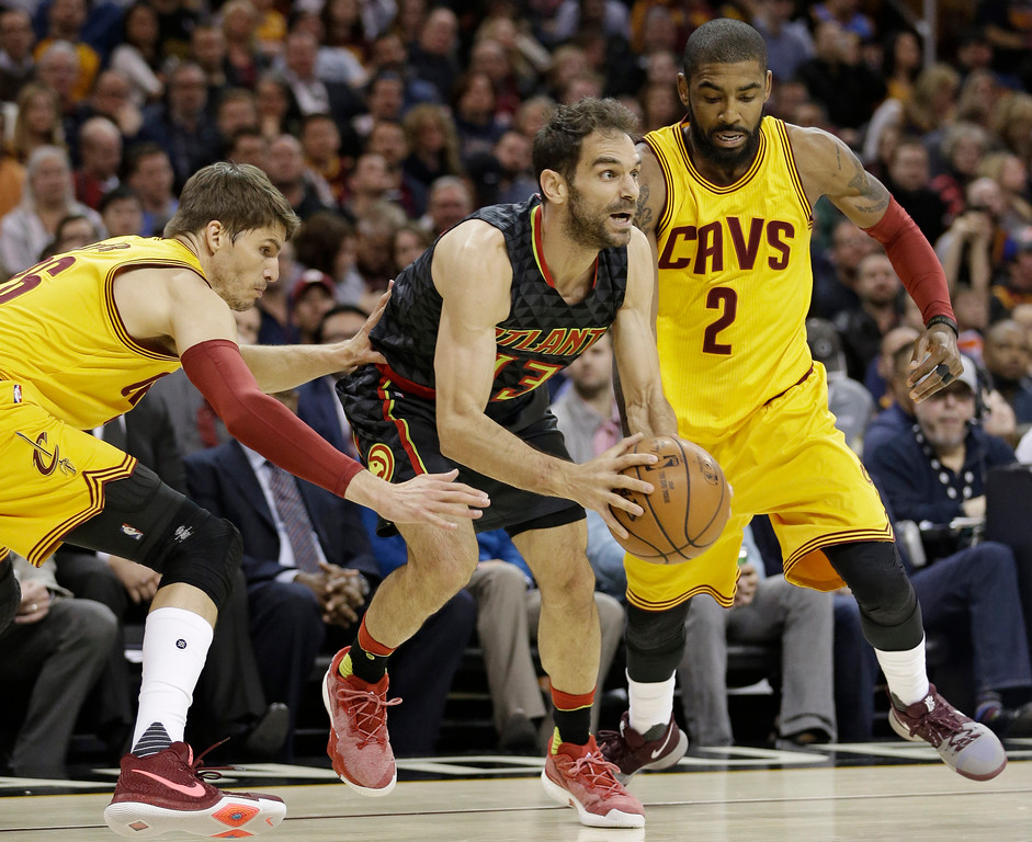 . Atlanta Hawks\' Jose Calderon, center, drives between Cleveland Cavaliers\' Kyle Korver, left, and Kyrie Irving in the first half of an NBA basketball game, Friday, April 7, 2017, in Cleveland. (AP Photo/Tony Dejak)
