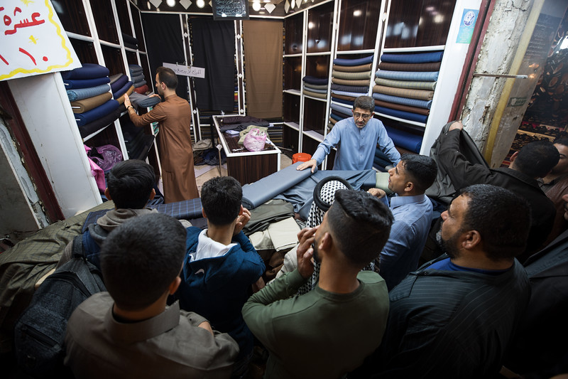 Men shopping for suit fabric at Najaf souq.