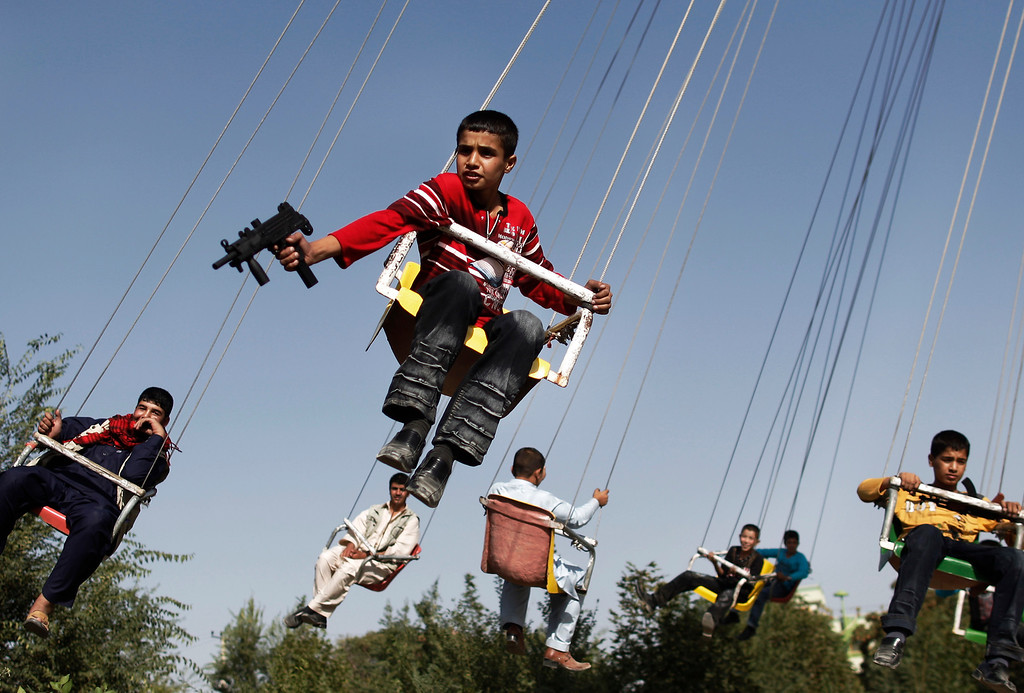 . In this Sunday, Sept. 20, 2009 file photo made by Associated Press photographer Anja Niedringhaus, an Afghan boy holds a toy gun as he enjoys a ride with others on a merry-go-round to celebrate the Eid al-Fitr festival, in Kabul, Afghanistan.(AP Photo/Anja Niedringhaus, File)