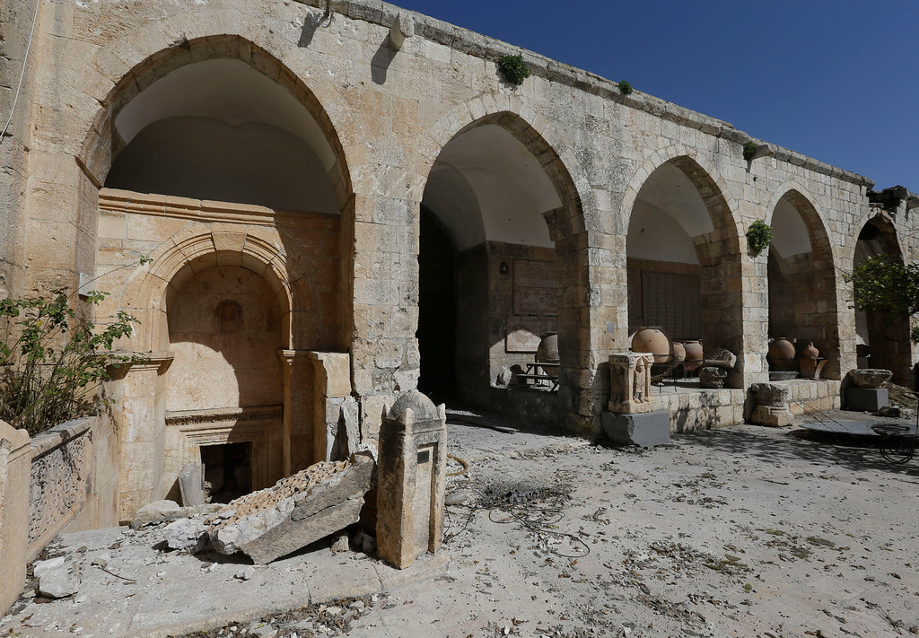 . In this photo taken Tuesday, Feb. 26, 2013, damage caused by shelling at a 17th-century caravanserai, which presently serves as a headquarters for the Free Syrian Army, in Maaret al-Numan, Idlib province, Syria. Across northern Syria, rebels, soldiers and civilians are making use of the country\'s wealth of ancient and medieval remains for protection. The structures are built of thick stone that has already withstood the ravages of centuries. They are often located in strategic spots overlooking towns and roads. (AP Photo/Hussein Malla)