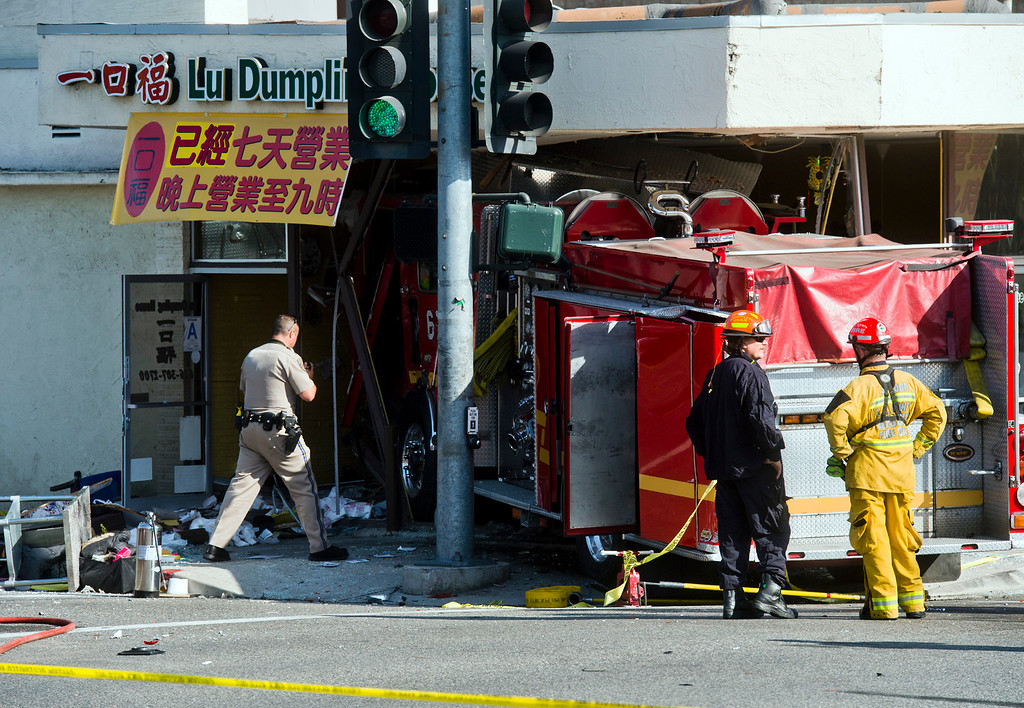 . Emergency personnel investigate the scene after a fire truck crashed into Lu Dumpling House restaurant in Monterey Park on Wednesday, April 16, 2014. (Photo by Watchara Phomicinda/ San Gabriel Valley Tribune)