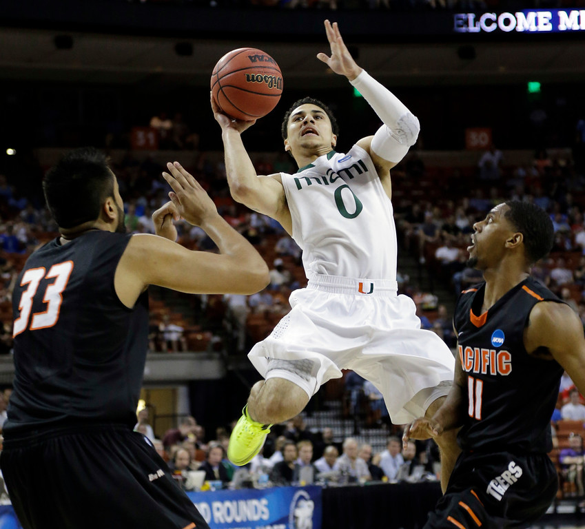 . Miami\'s Shane Larkin (0) shoots between Pacific\'s Tony Gill (33) and Lorenzo McCloud (11) during the first half of a second-round game of the NCAA college basketball tournament Friday, March 22, 2013, in Austin, Texas.  (AP Photo/David J. Phillip)