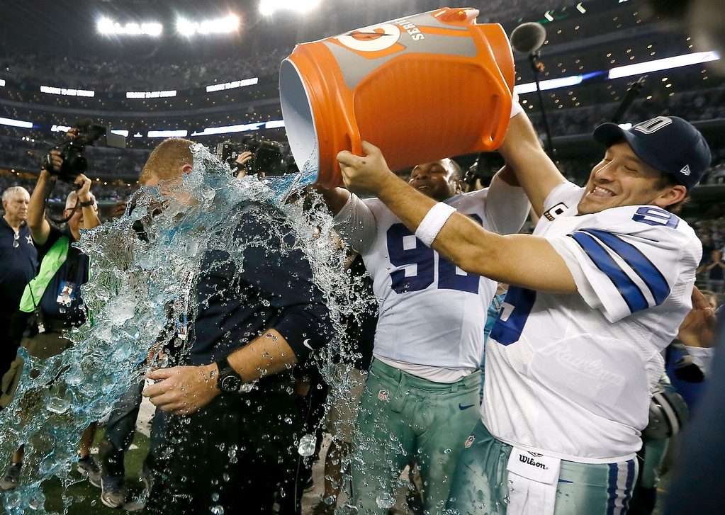 . Dallas Cowboys head coach Jason Garrett is doused by Dallas Cowboys\' Jeremy Mincey, center and quarterback Tony Romo, right, after their 42-7 win over the Indianapolis Colts in an NFL football game, Sunday, Dec. 21, 2014, in Arlington, Texas. (AP Photo/Brandon Wade)