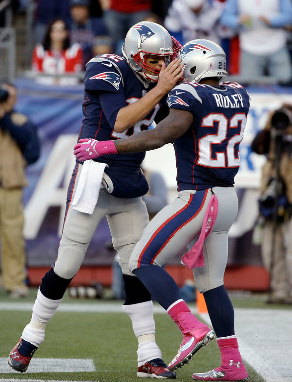 . New England Patriots quarterback Tom Brady, left, celebrates his touchdown pass to  running back Stevan Ridley (22) in the first half of an NFL football game against the New Orleans Saints Sunday, Oct. 13, 2013, in Foxborough, Mass. (AP Photo/Stephan Savoia)