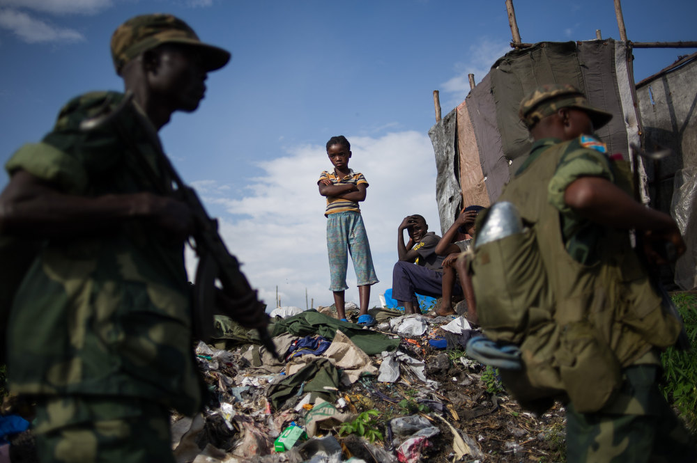 . A child watches as Congolese government army (FARDC) soldiers return to the military barracks in Goma eastern Democratic Republic of the Congo on December 3, 2012. Democratic Republic of Congo troops entered the eastern mining hub of Goma Monday, two days after rebel M23 fighters ended an almost fortnight-long occupation in line with a regionally brokered deal. The rebels are demanding that the Congolese government begin complex negotiations with them and have threatened to march back into Goma if Kinshasa reneges on a pledge they say was made to begin talks. PHIL MOORE/AFP/Getty Images