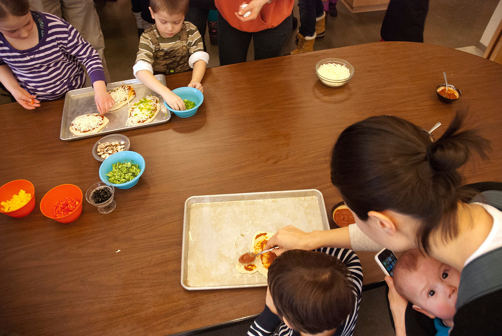 . Kayla Rice/Reformer MJ Iams, 3, of Brattleboro gets some help from his mother, Nara Iams and baby brother Patrick Iams while spreading tomato sauce on his pizza crust during a cooking class held at the Brattleboro Food Co-Op for the Winter Carnival on Friday afternoon.