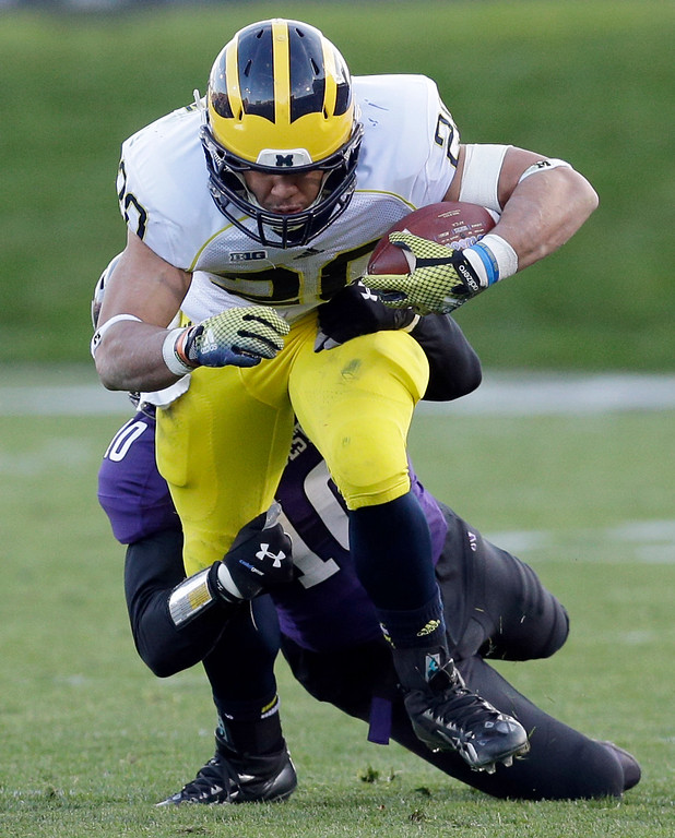 . Michigan running back Drake Johnson (20) is tackled by Northwestern safety Traveon Henry (10) during the first half of an NCAA college football game in Evanston, Ill., Saturday, Nov. 8, 2014. (AP Photo/Nam Y. Huh)
