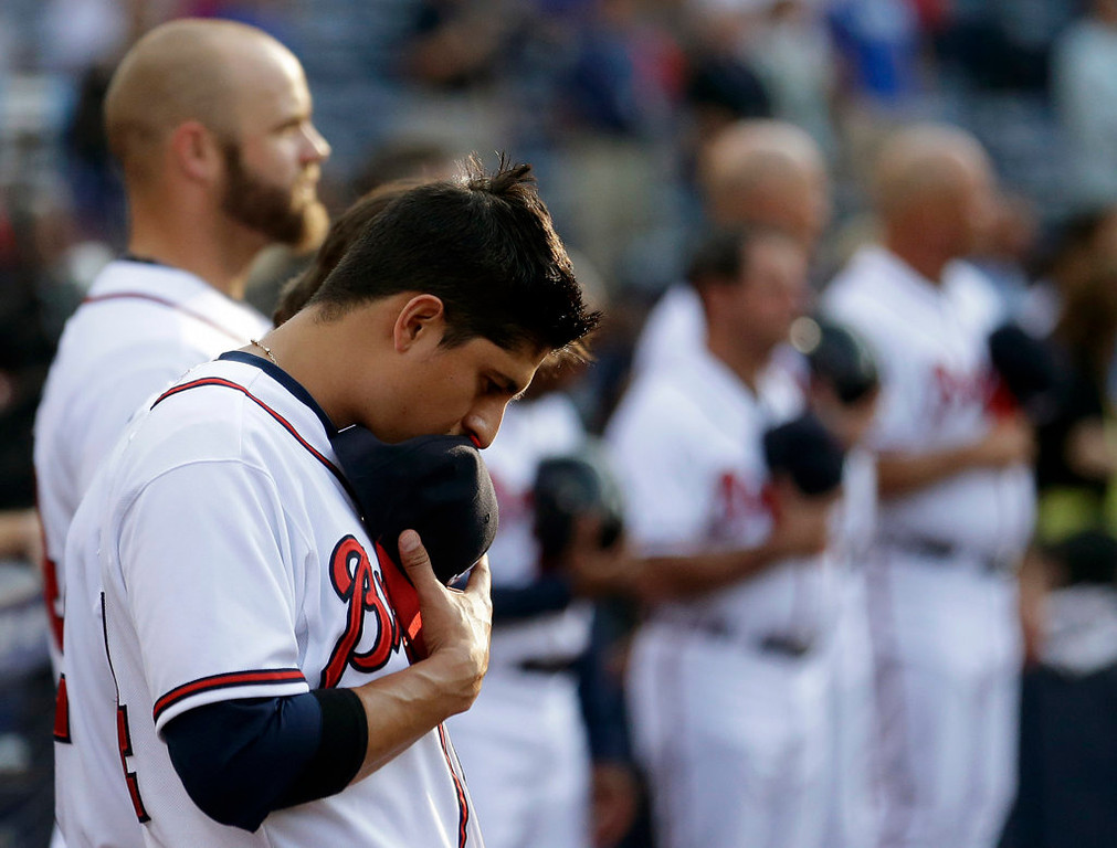 . Atlanta Braves shortstop Ramiro Pena, left, and his teammates pause for a moment of silence before the game for the victims of the Oklahoma tornado. (AP Photo/John Bazemore)