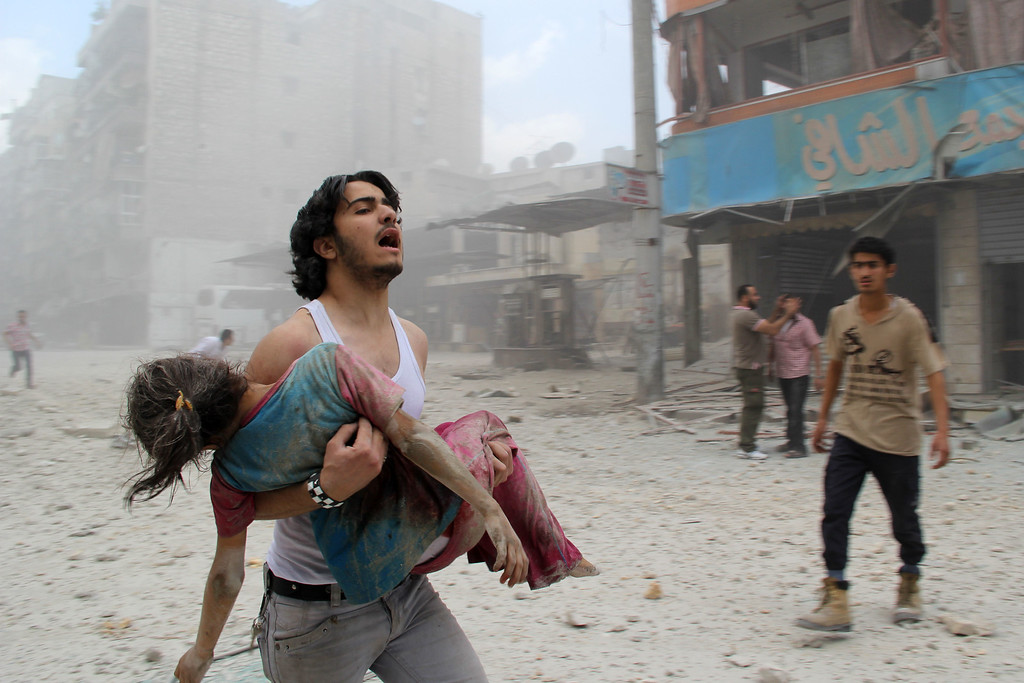 . A man carries a young girl who was injured in a reported barrel-bomb attack by government forces on June 3, 2014 in Kallaseh district in the northern city of Aleppo. Some 2,000 civilians, including more than 500 children, have been killed in regime air strikes on rebel-held areas of Aleppo since January, many of them in barrel bomb attacks. AFP PHOTO / BARAA  AL-HALABI/AFP/Getty Images