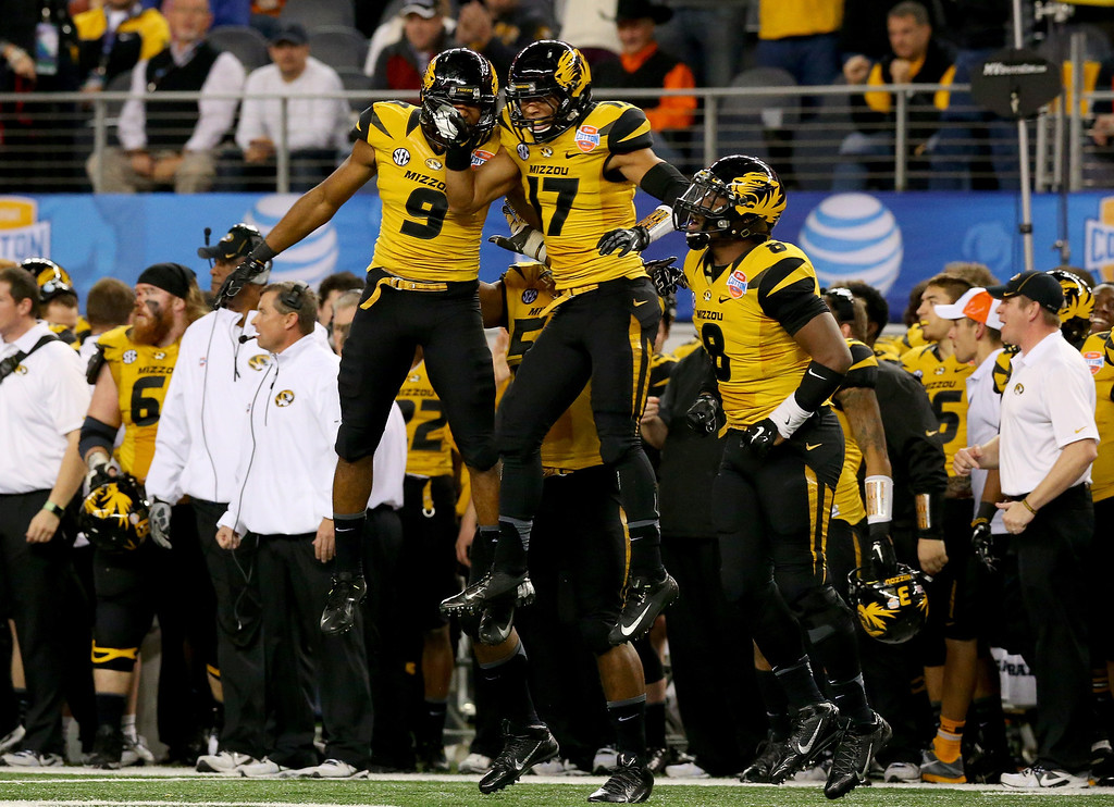 . ARLINGTON, TX - JANUARY 03:  Braylon Webb #9 of the Missouri Tigers celebrates with teammate Matt White #17 after Webb intercepts a pass in the third quarter against the Oklahoma State Cowboys during the AT&T Cotton Bowl on January 3, 2014 in Arlington, Texas.  (Photo by Ronald Martinez/Getty Images)