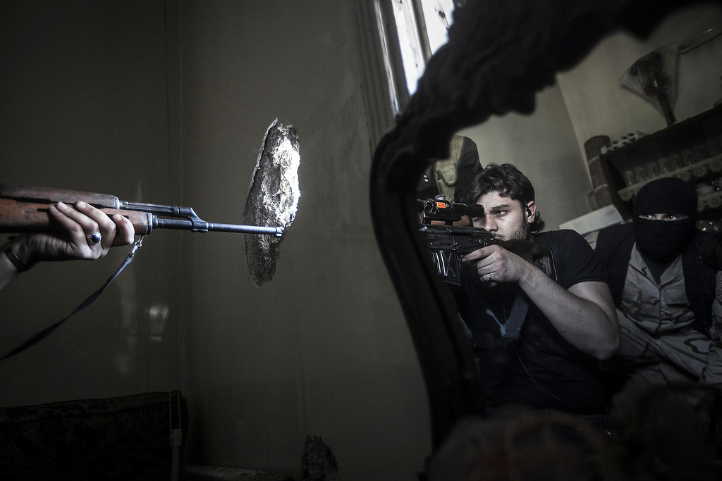. FILE - A rebel sniper aims at a Syrian army position, seen with another rebel fighter reflected in a mirror, in a residential building in the Jedida district of Aleppo, Syria on Monday, Oct. 29, 2012. (AP Photo/Narciso Contreras, File)