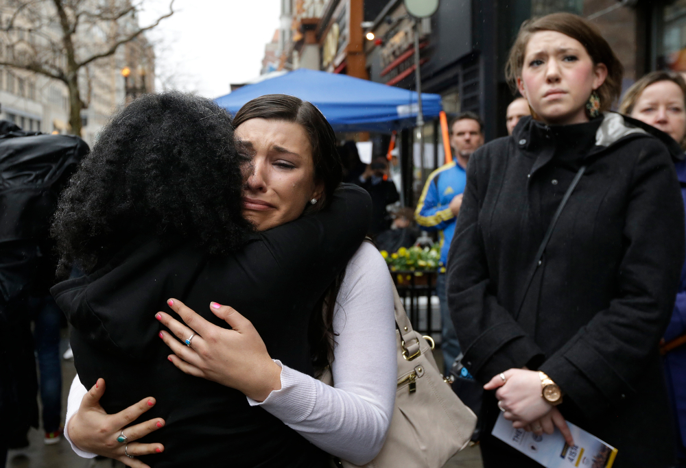 . Olivia Savarino, center, hugs Christelle Pierre-Louis, left, as Callie Benjamin, right, looks on near the finish line of the Boston Marathon during ceremonies on Boylston Street, Tuesday, April 15, 2014, in Boston. Savarino and Benjamin were working at the Forum restaurant when a bomb went off in front of the building on April 15, 2013. (AP Photo/Steven Senne)
