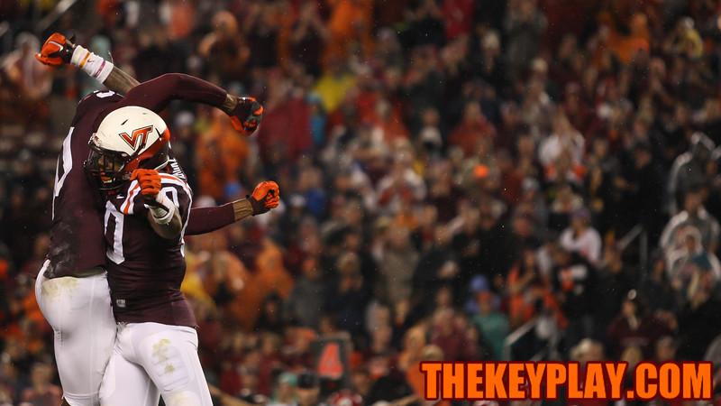 Deon Clarke and Dadi Nicolas celebrate a tackle for loss. (Mark Umansky/TheKeyPlay.com)