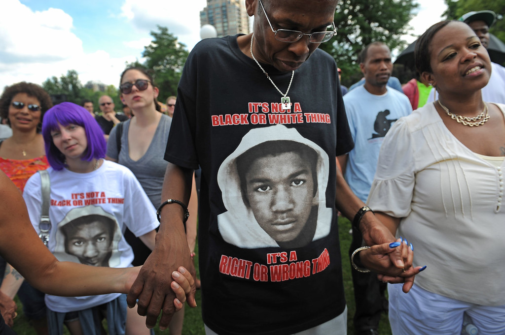 """. Emmitt Brooks, middle, lowers his head in prayer while holding hands with a Charnissa Staten, far right, near the end of the rally in City Park in Denver, CO on July 14, 2013.  Several hundred people turned out  to show their disappointment in the acquittal of George Zimmerman in the murder trail of Trayvon Martin.  Zimmerman is the Florida man who shot and killed Trayvon Martin. \""""We will not erase the conversation of race,\"""" said Jeff Fard, founder of Brother Jeff\'s Cultural Center in the Five Points neighborhood. \""""Don\'t be afraid to say if Trayvon Martin was a white man he would be alive today.\"""" Photo by Helen H. Richardson/The Denver Post)"""