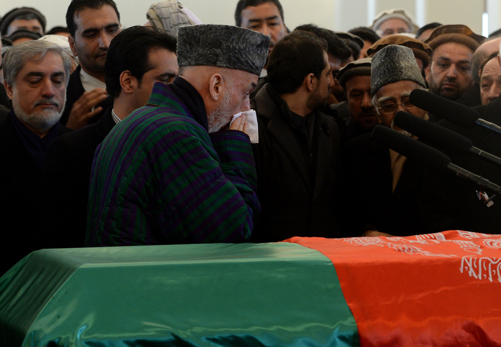 . Afghan President Hamid Karzai (C) pays his last respects as he prays with others at the flag-covered coffin of Afghan Vice-President Marshal Mohammad Qasim Fahim, formerly one of the country\'s most feared warlords during his burial ceremony at the Presidential Palace in Kabul on March 11, 2014. (SHAH MARAI/AFP/Getty Images)